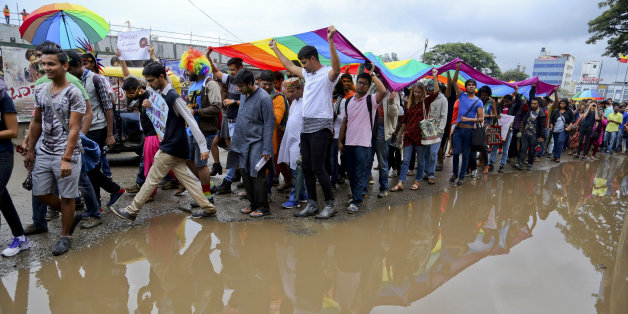 Members and supporters of lesbian, gay, bisexual and transgender community, hold a large rainbow flag as they walk past a puddle of rain water during a 'Pride March' rally in Bangalore, India, Sunday, Nov. 22, 2015. Gay rights supporters waved flags and danced past traffic during the march to celebrate gay pride and to push for the repeal of a colonial-era law that makes homosexuality a crime. (AP Photo/Aijaz Rahi)