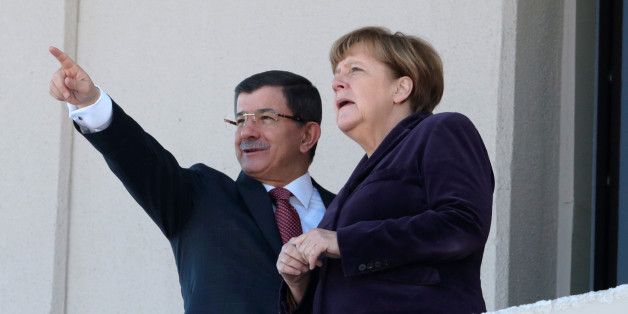 German Chancellor Angela Merkel, right, and Turkish Prime Minister Ahmet Davutoglu speak as they look towards the city center after a welcome ceremony in Ankara, Turkey, Monday, Feb. 8, 2016. Merkel is meeting Davutoglu and other Turkish officials for talks on reducing the influx of migrants to Europe. Turkey, a key country on the migrant route to Europe, is central to Merkel's diplomatic efforts to reduce the flow. (AP Photo/Burhan Ozbilici)