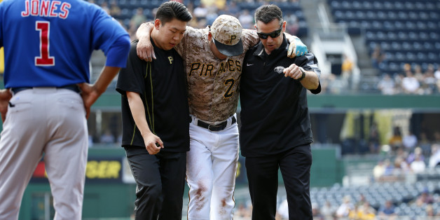 Pittsburgh Pirates' Jung Ho Kang, center, is helped off the field by  team trainer, right, and his interpreter after injuring his left leg turning a double play in the first inning of a baseball game against the Chicago Cubs in Pittsburgh, Thursday, Sept. 17, 2015. Kang left the game. (AP Photo/Gene J. Puskar)