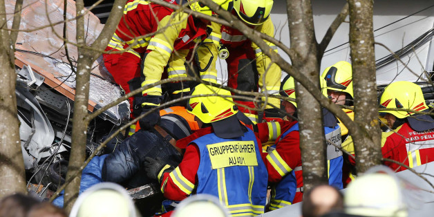 Rescue workers salvage a body at the site where two trains collided head-on near Bad Aibling, southern Germany, Tuesday, Feb. 9, 2016. Several people have been killed and dozens were injured. (AP Photo/Matthias Schrader)