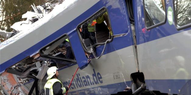 Ein Helfer steht an dem verunglückten Zug in Bad Aibling