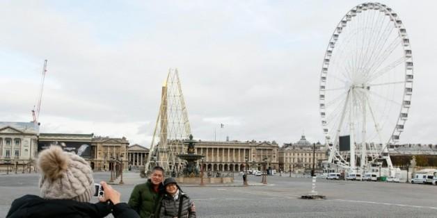 Des touristes prennent la pose devant la place de la Concorde à Paris le 30 novembre 2015