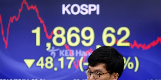 A currency trader walks by the screen showing the Korea Composite Stock Price Index (KOSPI) at the foreign exchange dealing room in Seoul, South Korea, Thursday, Feb. 11, 2016. Asian stocks shuddered again Thursday, led by sharp drops in Hong Kong and South Korea, which were catching up to global market turmoil after being shut for Lunar New Year holidays.(AP Photo/Lee Jin-man)