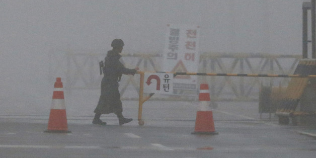 "A South Korean Army soldier adjusts barricade on a foggy and rainy morning at Unification Bridge near the border village of Panmunjom in Paju, South Korea, Friday, Feb. 12, 2016. North Korea on Thursday ordered a military takeover of a factory park that had been the last major symbol of cooperation with South Korea, calling Seoul's earlier suspension of operations at the jointly run facility as punishment for the North's recent rocket launch a ""dangerous declaration of war."" (AP Photo/Lee Jin-man)"