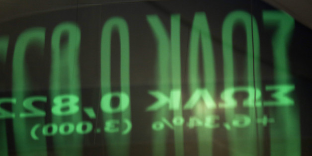 A reflection of share prices on an electronic ticker screen sits on a glass door panel inside the Athens Stock Exchange on Wednesday, Aug. 5, 2015. Greece's government aims to reach agreement with creditors on a new bailout within the next two weeks, enabling it to make a 3.2 billion-euro ($3.5 billion) payment to the European Central Bank without further bridge financing. Photographer: Kostas Tsironis/Bloomberg via Getty Images