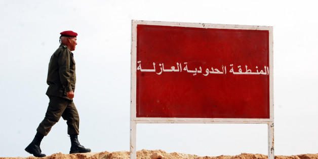 """A Tunisian soldier walks on a sandbank near a board saying """"no-man's land, buffer zone"""" during a presentation of the anti-jihadi fence, in near Ben Guerdane, eastern Tunisia, close to the border with Libya, Saturday, Feb. 6, 2016. Tunisia's defense minister has visited an anti-jihadi fence that's being built on the country's border with Libya to stop Islamist militants from entering Tunisian territory. Defense Minister Farhat Horchani inspected the first completed part of the 196-kilometer (122-"""