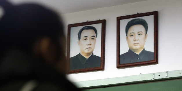 A visitor tours near the pictures of North Korean founder late Kim Il Sung, left, and his son, leader late Kim Jong Il at the exhibition hall of the unification observatory in Paju, South Korea, Wednesday, Feb. 10, 2016. South Korea says it will suspend the operations at a joint industrial park with North Korea in response to the North's recent rocket launch.(AP Photo/Lee Jin-man)