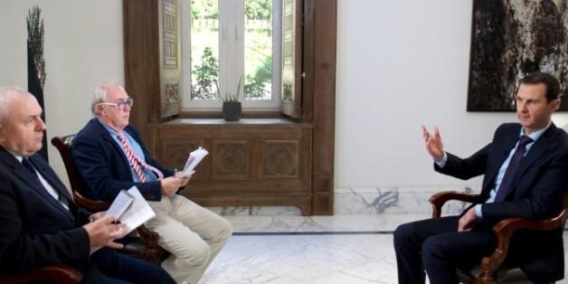 Une photo fournie par le service de presse de la présidence syrienne, montre Bachar al-Assad avec les deux journalistes de l'AFP, Christian Chaise (G) et Sammy Ketz (2ème), le 11 février 2016 à Damas
