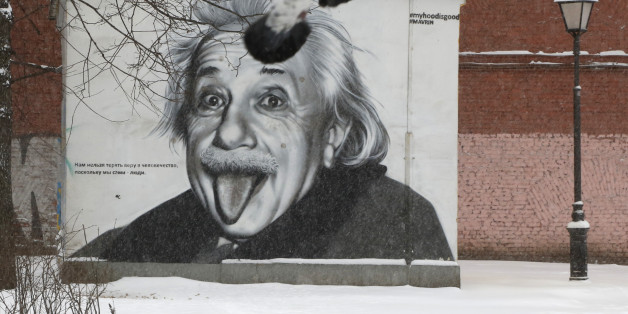 Pigeons fly past a portrait of Albert Einstein painted on a wall in St.Petersburg, Russia, Tuesday, Jan. 12, 2016. Low temperatures caused the two-days of snowfall in St.Petersburg. (AP Photo/Dmitry Lovetsky)