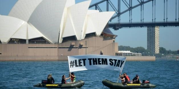 """Des militants de Greenpeace brandissent une banderole avec l'inscription """"#LET THEM STAY"""" (""""#Laissez les rester"""") devant l'opéra de Sydney, le 14 février 2016, alors qu'un hôpital australien refuse de renvoyer un bébé dans un camp de réfugiés controversé"""