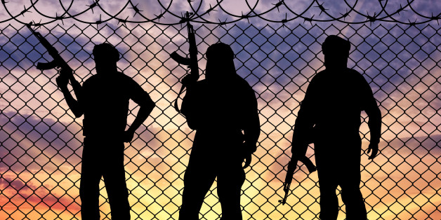 Concept of terrorism. Silhouette terrorists near the border fence in the background at sunset