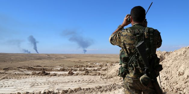 A member of a coalition force, which includes People's Protection Units (YPG) Women's Protection Units (YPJ), Sutoro militia, a pro-government Syriac Christian movement, and other forces, monitors the horizon in al-Hol in the Syrian Hasakeh province, some 650 kms northeast of Damascus, near the Iraqi border on November 2, 2015. AFP PHOTO / DELIL SOULEIMAN / AFP / DELIL SOULEIMAN        (Photo credit should read DELIL SOULEIMAN/AFP/Getty Images)