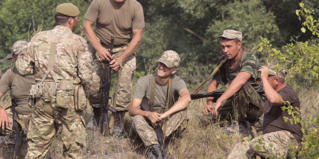 British servicemen, left, instruct Ukrainian soldiers during training exercises on the military base outside Zhitomir, Ukraine, Tuesday, Aug. 11, 2015. (AP Photo/Efrem lukatsky)