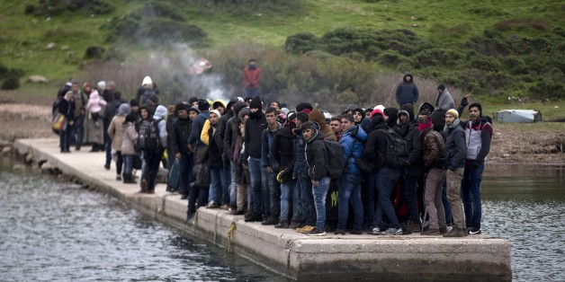 FILE - In this photo taken on Wednesday, Jan. 20, 2016,  migrants who have arrived at the shore of the deserted Greek island of Pasas wait for the Coast Guard to transport them to Oinousses island. NATO's European commander on Thursday, Feb. 11, 2016, ordered three warships to move immediately to the Aegean Sea to help end the deadly smuggling of migrants between Turkey and Greece. (AP Photo/Petros Giannakouris, File)