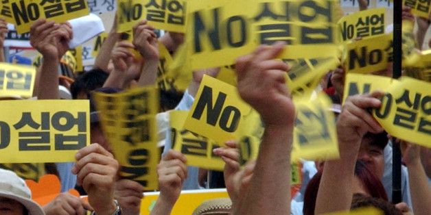 "Jobless workers show a cards during an anti-government rally demanding job security at a park in Seoul, Friday, June 11, 2004. The nation's employment capacity dipped to the worst level in six years since the financial crisis six years ago as the economy loses momentum to generate extra jobs in accordance with growth. The letters on the cards read "" Unemployment "".(AP Photo/Ahn Young-joon)."