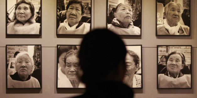 "FILE - In this Feb. 3. 2014 file photo, a visitor looks at portraits of late former ""comfort women"" who were forced to serve for the Japanese troops as a sexual slave during World War II, at the House of Sharing, a nursing home and museum for 10 former sex slaves, in Toechon, South Korea. What's in a word? As Japan's leader Shinzo Abe prepares to issue a statement Friday, Aug. 14, 2015 to mark the 70th anniversary of the end of World War II, attention is focused on the words he will us"