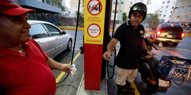 A motorcyclist pays about two Bolivars (3 cents of a dollar) after filling his scooter's tank at a gas station in Caracas, Venezuela, Wednesday, Feb. 17, 2016. Venezuela's government is raising gasoline prices sixtyfold, the first increase of any kind in more than 17 years as the country struggles with an economic collapse. Yet drivers will still be able to fill their tanks for pennies. (AP Photo/Fernando Llano)