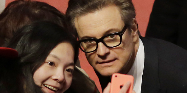 Actor Colin Firth poses for photographs with fans upon arrival at the red carpet of the film 'Genius' during the 2016 Berlinale Film Festival in Berlin, Tuesday, Feb. 16, 2016. (AP Photo/Markus Schreiber)