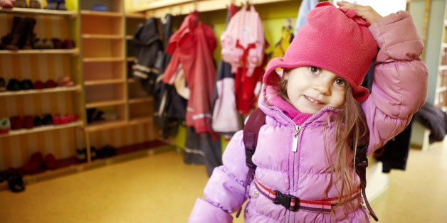 Little girl in nursery with anorak and cap