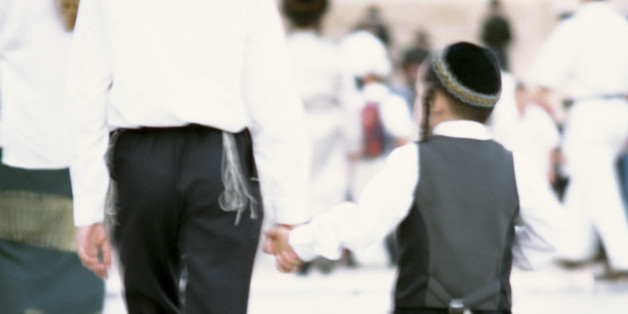 Israel, Jerusalem, two Orthodox Jewish boys wearing kippas and holding hands, rear view