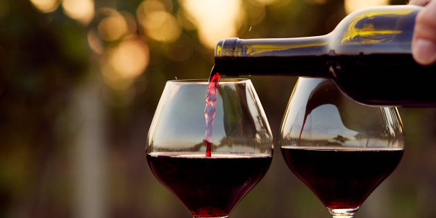 Pouring red wine into glasses in the vineyard, toned