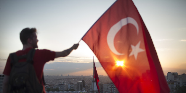 Ein Mann zeigt auf einer Demonstration die türkische Flagge
