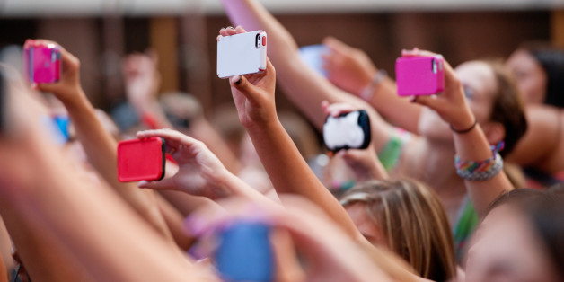 Side view of a group of people in a crowd using different brands and colors of mobile phones (cellphones).