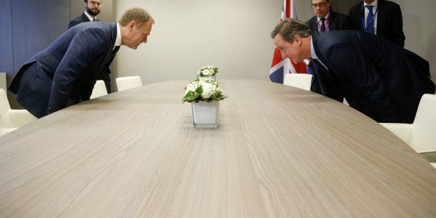 British Prime Minister David Cameron, right, takes his seat with European Council President Donald Tusk, left, during a bilateral meeting on the sidelines of an EU summit in Brussels on Thursday, Feb. 18, 2016. European Union leaders are holding a summit in Brussels on Thursday and Friday to hammer out a deal designed to keep Britain in the 28-nation bloc.  (Olivier Hoslet, Pool Photo via AP)