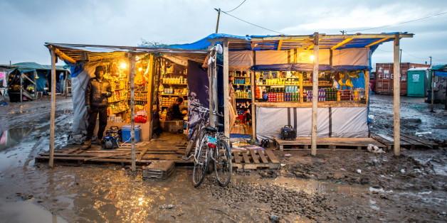 """Ein Flüchtling steht vor einem provisorischen Geschäft, das Asylbewerber im """"Dschungel"""" von Calais errichtet haben (Archivbild)"""
