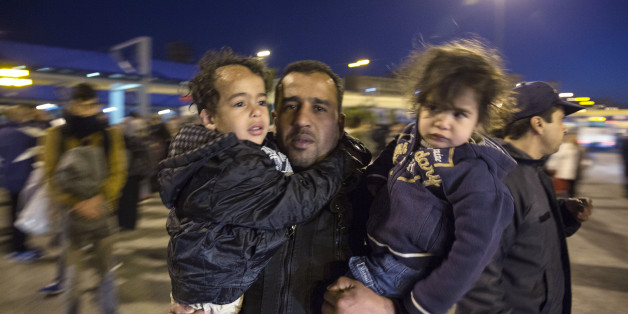 A man carrying two children arrives at the port of Piraeus, near Athens, on Saturday, Feb. 20, 2016. EU leaders at a summit in Brussels made little headway in the elusive search for joint solutions to the influx of refugees and other migrants, though they did agree to hold a meeting in early March with Turkey.  (AP Photo/Yorgos Karahalis)