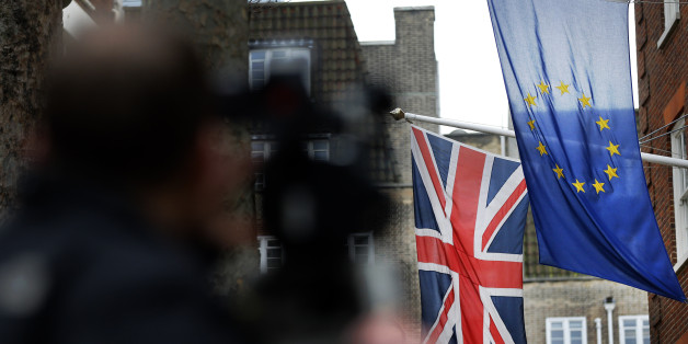 A camera man films the EU flag beside the Union flag at Europa House in London, Wednesday, Feb. 17, 2016. Britain's Prime Minister, David Cameron, will attend an EU summit in Brussels starting Thursday. (AP Photo/Frank Augstein)