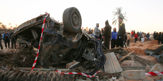 In this Friday, Feb. 19, 2016 photo, people gather by the wreckage of a car, after an air strike on a house and training camp belonging to the Islamic State group, west of Sabratha, Libya. American F-15E fighter-bombers struck an Islamic State militant training camp in rural Libya near the Tunisian border Friday, killing dozens, probably including an IS operative considered responsible for deadly attacks in Tunisia last year, U.S. and local officials said. (AP Photo/Mohamed Ben Khalifa)