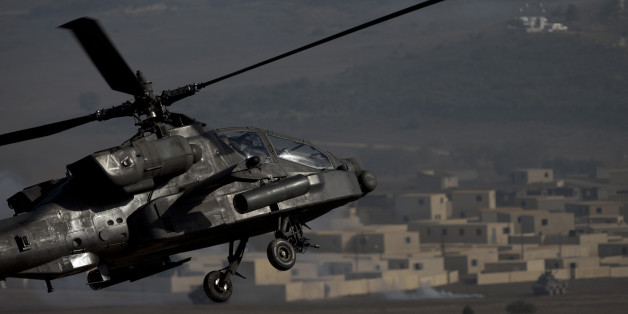 A US AH-64 Apache flies over the combat zone during a NATO military demonstration in Zaragoza, Spain, Wednesday Nov. 4, 2015. NATO is putting on its most fearsome display of military might in over a decade with soldiers, ships and planes meant to hone and test its abilities as well as send an unequivocal sign to Russia and other real or potential foes. For three weeks which started Oct. 21, more than 36,000 personnel from all 28 NATO allies and eight partner nations, 160 aircraft and 60 ships will be taking part in exercises across a wide swath of southern Europe from Portugal to Italy. (AP Photo/Abraham Caro Marin)