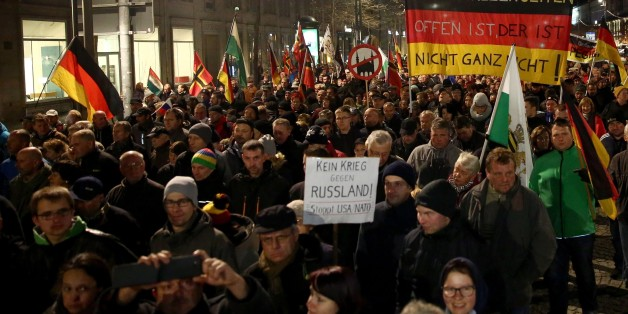 DRESDEN, GERMANY - NOVEMBER 02: A group of people, led by far right movement PEGIDA (Patriotic Europeans Against the Islamisation of the Occident) gather on a demonstration against 'Islam' and immigrants at Neumarkt Square in Dresden, Germany on October 02, 2015. (Photo by Mehmet Kaman/Anadolu Agency/Getty Images)