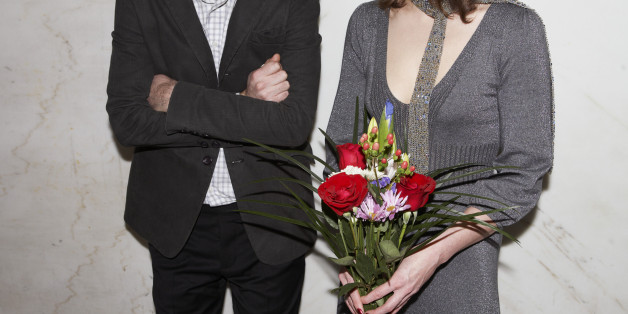 Couple with arms crossed man and woman holding flowers