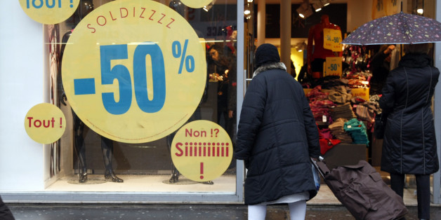 """A woman looks at a shop with """"Soldes"""", Sales written on the window in Paris, France, Wednesday, Jan. 12, 2011.  Parisians  search over the bargain bin for deals as during the  winter sales in France. (AP Photo/Francois Mori)"""