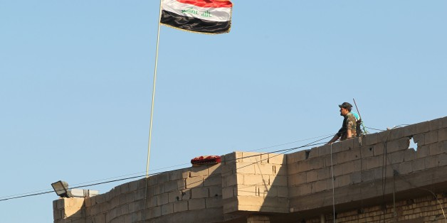 A member of Iraqi security forces stands on a roof on February 12, 2016, after security forces retook the eastern outskirts of Ramadi city from Islamic State (IS) group jihadists.