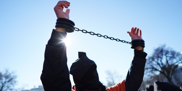A demonstrator raises his shackled wrists during a protest calling for the closure of the Guantanamo Bay US Naval Prison on January 11, 2016 in front of the White House in Washington, DC. US President Barack Obama is expected to present his plan on closing the facility during his final State of the Union address. AFP PHOTO/MANDEL NGAN / AFP / MANDEL NGAN        (Photo credit should read MANDEL NGAN/AFP/Getty Images)