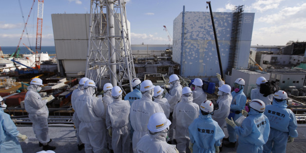 Members of the media tour group, wearing protective suits and masks, receive a briefing from Tokyo Electric Power Co. (TEPCO) employees (in blue) in front of the No. 1, left,and No. 2 reactor buildings at the tsunami-crippled Fukushima Dai-ichi nuclear power plant in Okuma, Fukushima Prefecture, northeastern Japan, Wednesday, Feb. 10, 2016. In one month, Japan is marking the fifth anniversary of a devastating earthquake and tsunami that hit on March 11, 2011 and left nearly 19,000 people dead or
