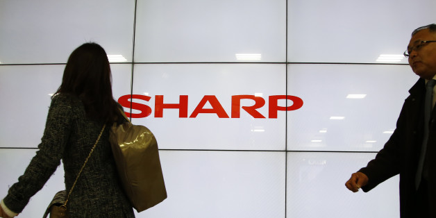 People walk past the log of Sharp Corp. in Tokyo, Thursday, Feb. 25, 2016. Troubled Japanese electronics maker Sharp has agreed to a takeover offer from Taiwanese company Hon Hai, also known as Foxconn, Japanese media reported Thursday. (AP Photo/Shizuo Kambayashi)