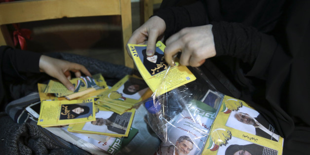 An election campaign worker makes packages of leaflets of a group of conservative candidates in the upcoming parliamentary elections during a gathering in Tehran, Iran, Monday, Feb. 22, 2016. Iranians will vote for their representatives at the 290-seat parliament, as two major camps of conservatives and a coalition of reformists and moderates compete to win the majority of the house. On the same day as the parliamentary elections, polling for the Assembly of Experts, a 88-member clerical body in charge of selecting the country's supreme leader, will take place. (AP Photo/Vahid Salemi)