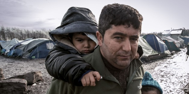 TOPSHOT - A man and his children from Iraq poses in the so-called 'Jungle' migrant camp in Gande-Synthe where 2,500 refugees from Kurdistan, Iraq and Syria live on February 11, 2016 in Grande-Synthe near the city of Dunkirk, northern France. / AFP / PHILIPPE HUGUEN        (Photo credit should read PHILIPPE HUGUEN/AFP/Getty Images)