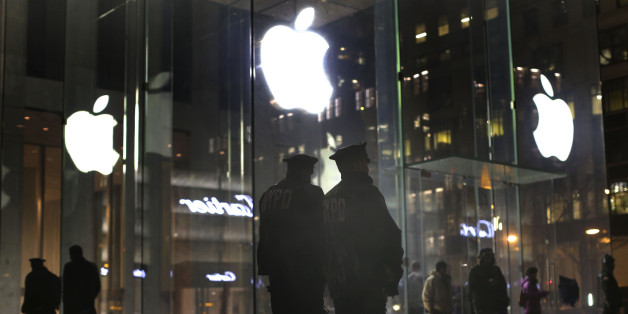 New York police officers stand outside the Apple Store on Fifth Avenue while monitoring a demonstration, Tuesday, Feb. 23, 2016, in New York.  Protesters assembled in more than 30 cities around the world to lash out at the FBI for obtaining a court order that requires Apple to make it easier to unlock an encrypted iPhone used by a gunman in December's mass murders in California. (AP Photo/Julie Jacobson)