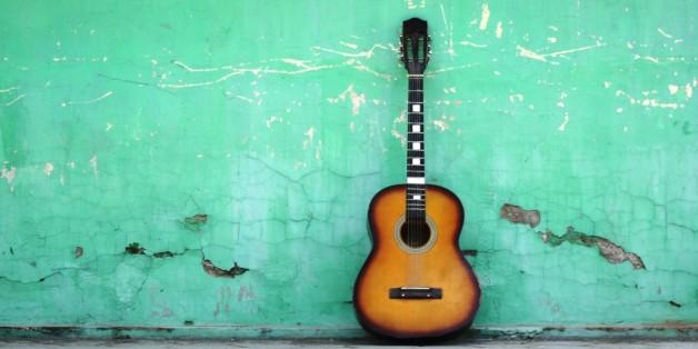 Eine Gitarre lehnt an einer Hauswand