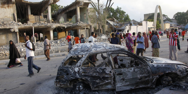 Somalis walk near destroyed buildings and the wreckage of a car, Saturday, Feb. 27, 2016 after a suicide car bomb Friday night in Mogadishu, Somalia. A suicide bomber rammed his car into the SYL hotel's entrance in Mogadishu and blew it up, allowing gunmen to fight their way past hotel guards at the first security barrier, said Capt. Mohamed Hussein. (AP Photo/Farah Abdi Warsameh)