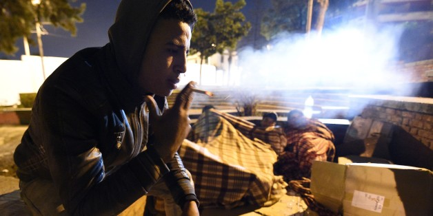 A Moroccan homeless youth smokes as his friends wrapped in blankets attempt to sleep, in a corner of a street in the northeastern coastal city of Tangier, on January 28, 2016. Having left their homes due to precarious social circumstances, some of these children attempt to travel to Europe by jumping on the back of a truck or a bus at the port of the city, in hope of finding a better life elsewhere. Drug addiction is very common among street children who commonly sniff glue and other chemicals to help them bear hunger and cold.  / AFP / FADEL SENNA        (Photo credit should read FADEL SENNA/AFP/Getty Images)