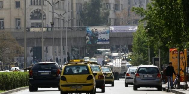Des véhicules circulent dans une rue de Damas le 27 février 2016