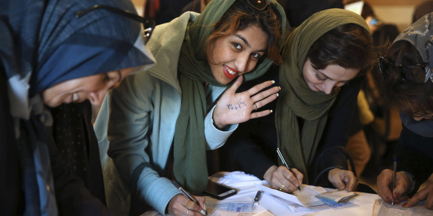 An Iranian woman displays her ink-stained finger after voting in the parliamentary and Experts Assembly elections at a polling station in Qom, 125 kilometers (78 miles) south of the capital Tehran, Iran, Friday, Feb. 26, 2016.  Polls opened Friday in Iran's parliamentary elections, the country's first since its landmark nuclear deal with world powers last summer. (AP Photo/Ebrahim Noroozi)