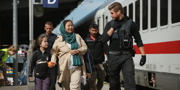 FREILASSING, GERMANY - SEPTEMBER 16:  A German policeman escorts a family from Afghanistan, who had arrived with migrants on a regular train from Vienna, Austria, and told to disembark by German police, to board a government-chartered train for the German state of North Rhine-Westphalia on September 16, 2015 in Freilassing, Germany. German authorities have temporarily reinstated border controls along Germany's border to Austria and are using Freilassing as a hub for managing migrants arriving by train from Austria and the Balkans. Germany is still accepting up to thousands of new migrants daily but has imposed border controls in order to crack down on smugglers and to better regulate the flow of arriving migrants, tens of thousands of whom arrived in Germany over the last few weeks. Meanwhile Hungary has sealed it new fence along its border to Serbia and is ferrying remaining migrants to izs border with Austria.  (Photo by Sean Gallup/Getty Images)
