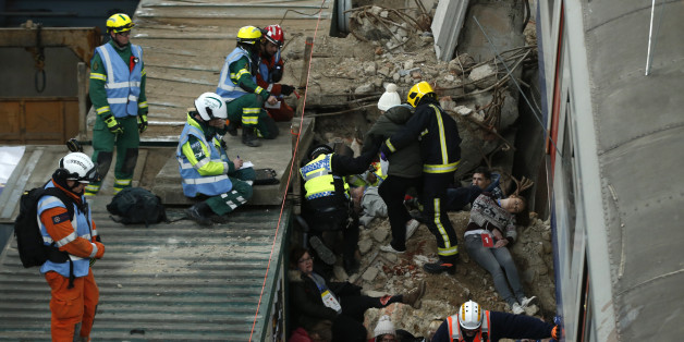 Evaluators on the roof of a container watch to see how members of the emergency services treat simulated casualties during an exercise run by the London Fire Brigade at a disused power station in east London, Monday, Feb. 29, 2016. The exercise involving the London emergency services is set around a building collapse onto a major London underground railway station. (AP Photo/Alastair Grant)